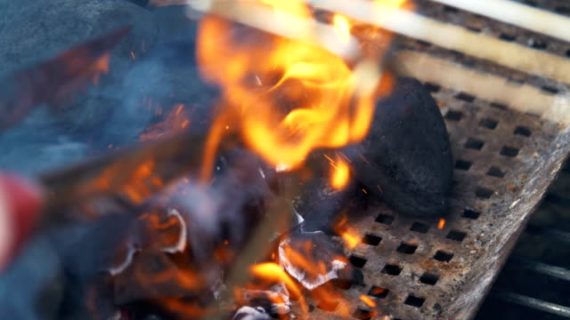 Wood charcoal burning on a grill in 4K Slow motion video