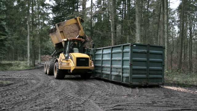 Wood chip transporter unload Long shot of wood chip transporter unloading wood chips into a container. biomass renewable energy source stock videos & royalty-free footage