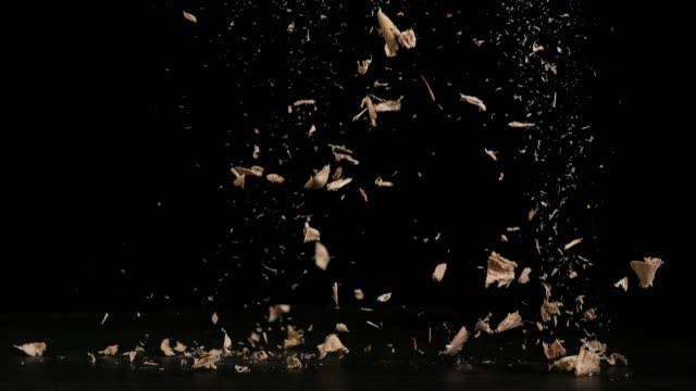 trucioli di legno che cadono sullo sfondo nero, slow motion 4k - segatura video stock e b–roll