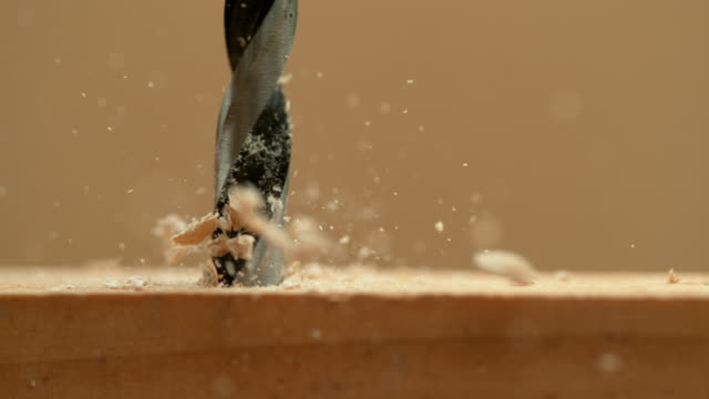 MACRO: Wood chips fly off a plank as handyman drills holes into the workpiece.