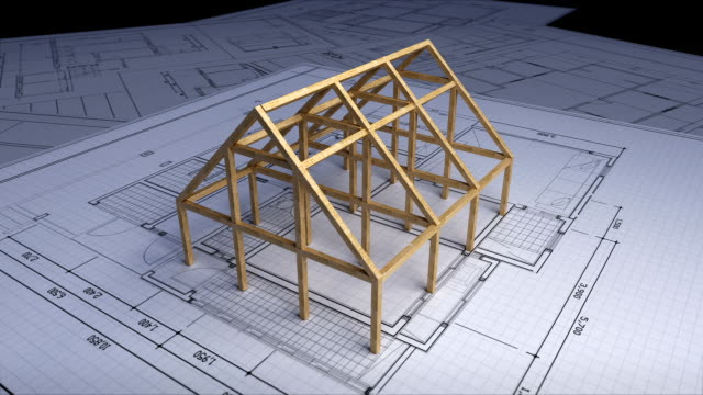 Wood frame making house on architectural design plan paper.