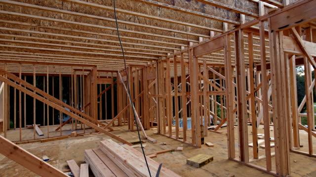 vídeos de stock e filmes b-roll de wood home framing at construction building frame structure on a new development - obras em casa janelas