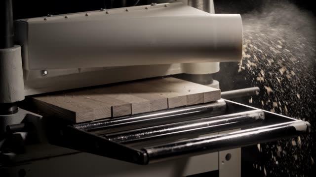 holz maschine verarbeitet board. nahaufnahme mit fliegenden sägemehl - bandsäge stock-videos und b-roll-filmmaterial