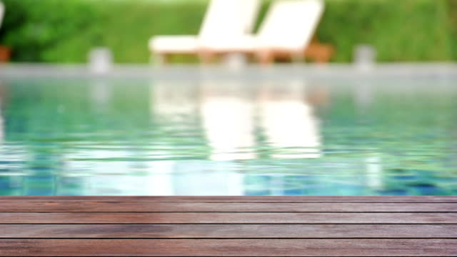 Wood plank on rippled swimming pool water background