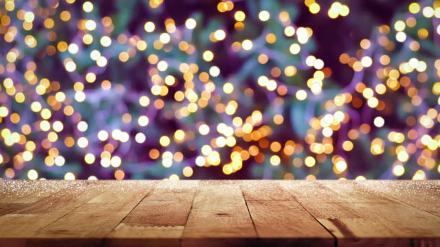 Wood table top with blinking decorative light bokeh on Christmas tree at night in background video