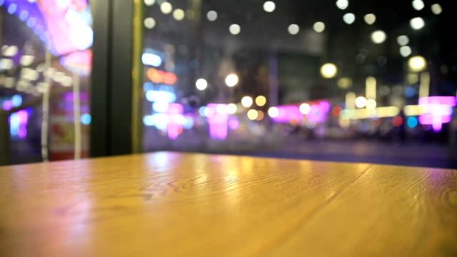 stockvideo's en b-roll-footage met houten tafelblad met wazig licht in de nacht - restaurant table
