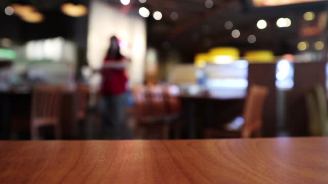 Wood table top with Restaurant cafe or coffee shop interior with people abstract defocused blur background Wood table top with Restaurant cafe or coffee shop interior with people abstract defocused blur background bar counter stock videos & royalty-free footage