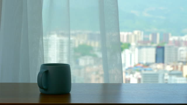 vídeos de stock e filmes b-roll de wood table with coffee cup in front of window - living room background