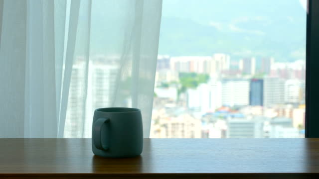 Wood table with coffee cup in front of window