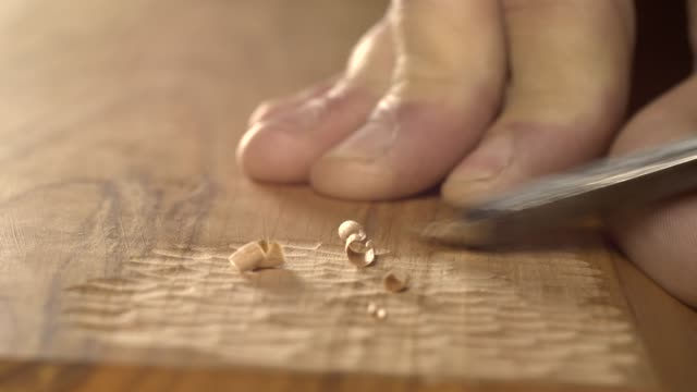 woodcarver carves a chisel notch in the board video