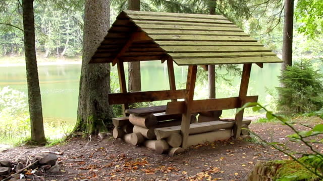 Wooden arbor for rest and picnic on the shore of a forest lake in the Carpathians video