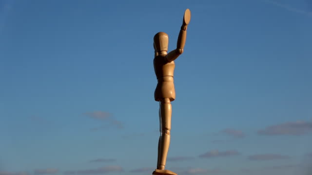 Wooden artist  manikin rotating on blue sky background video