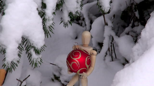 Wooden artist models with Christmas baubles Wooden artist models with Christmas baubles under snow covered fir tree marionette stock videos & royalty-free footage