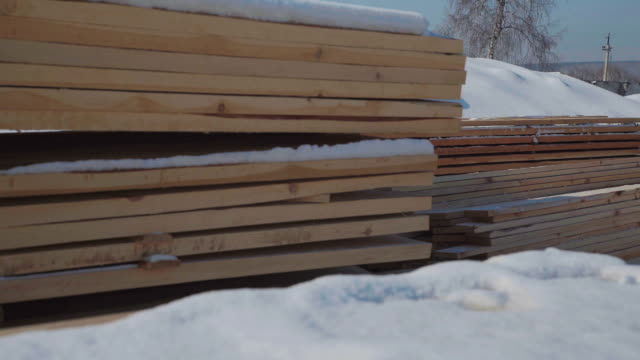 Wooden beams and boards neatly stacked in a pyramid shape video