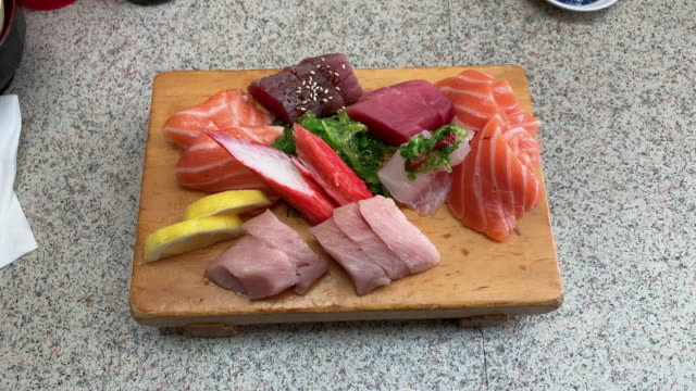 A Wooden Board of Different Cuts of Sashimi (Sushi) Sitting on a Kitchen Counter