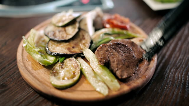 Wooden board with grilled meat and vegetables video