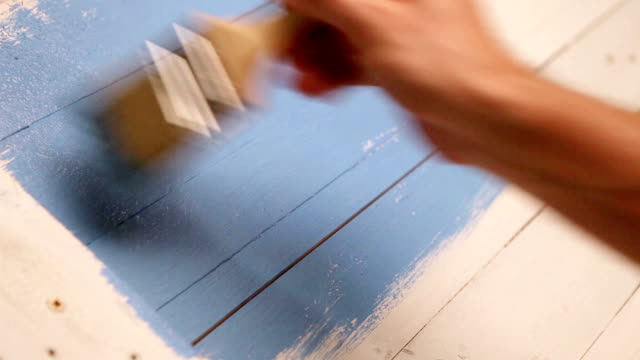 Wooden board's painting process: an artist applies blue colour with a brush video