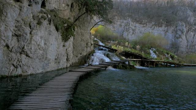 wooden boardwalk over waterfall at plitvice park - хорватия стоковые видео и кадры b-roll