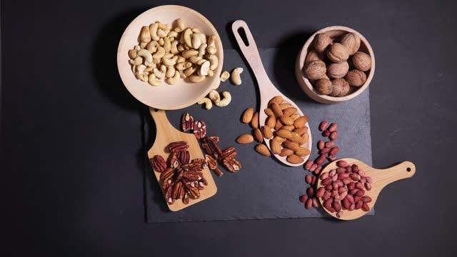 träskål med blandade nötter. hälsosam mat och mellanmål. valnöt, jordnötter, mandel, hasselnöt och cashewnötter. - pinjenöt bildbanksvideor och videomaterial från bakom kulisserna