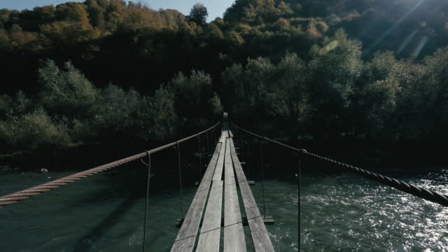Wooden bridge over a river on the trail in Carpathian mountains