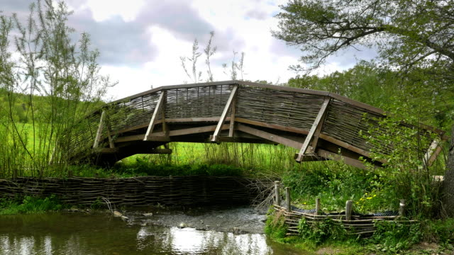 Wooden bridge over creek with braided wicker railing video