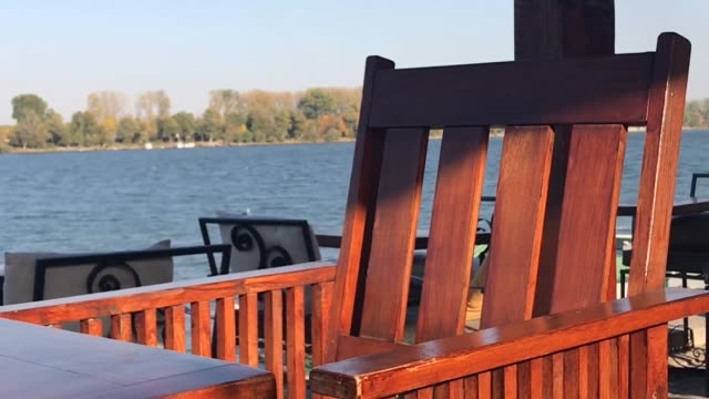 Wooden chair in focus with Danube river in background