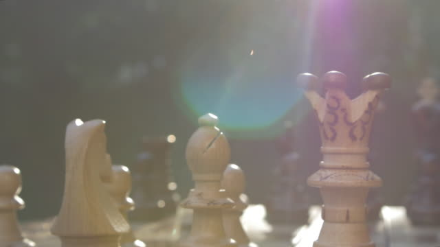 vídeos de stock e filmes b-roll de wooden chess game on a table in a camera slide from left to right against sun with lens flare - terreno