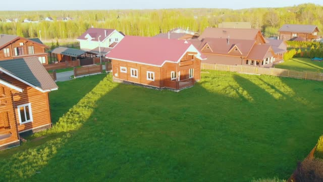 wooden cottage houses with red roofs and fresh green lawns video