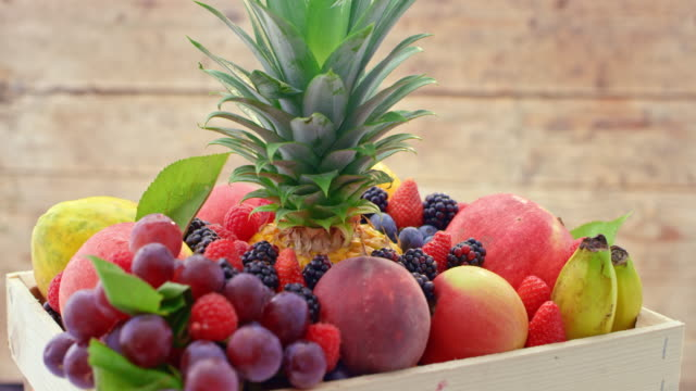 LD A wooden crate full of fresh fruits turning on the table