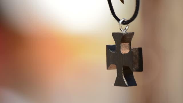 stockvideo's en b-roll-footage met houten kruis in lederen ketting hangen - halsketting