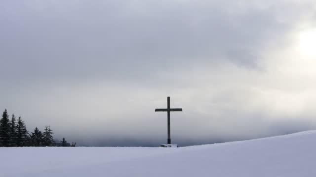 Wooden cross in snow above the dramatic sky with clouds and sunlight in winter. Time lapse.