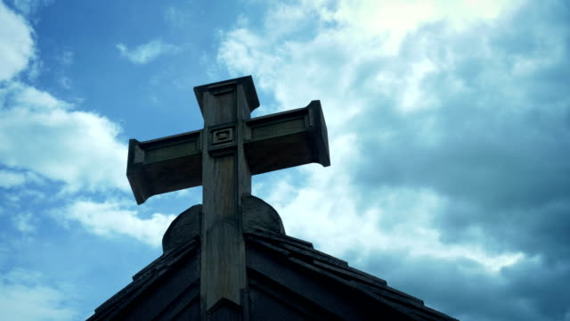 Wooden Cross On Building With Passing Clouds