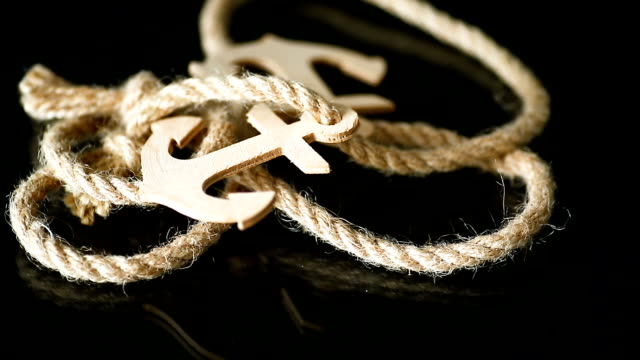 wooden decorative anchor with rope on black - postcard стоковые видео и кадры b-roll