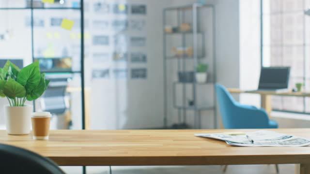Holztisch im Creative Bright Office. Im Hintergrund Professioneller junger Mann, der am Computer arbeitet – Video
