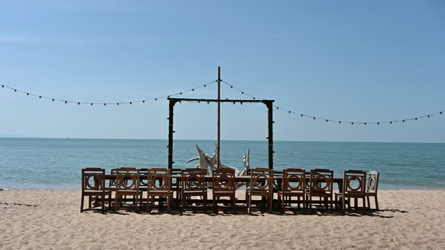 Wooden dining table with chairs and light bulb decoration on the beach in tropical sea