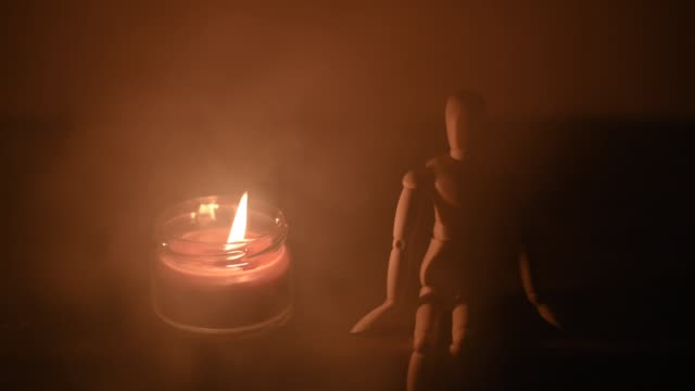 wooden doll on a black background in the light of a candle in a jar wooden doll on a black background in the light of a candle in a jar 1 marionette stock videos & royalty-free footage