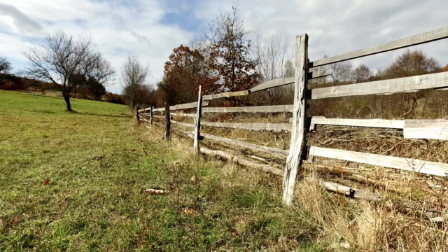 A Wooden Farm Fence and Autumn Colours, Tree with no leaves, Country crane shoot video