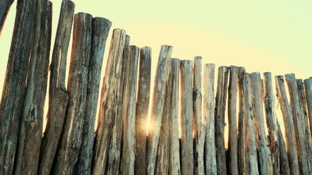 holzzaun aus großen stämmen in den hintergrund sonnenuntergang mit sunflare - verbogen stock-videos und b-roll-filmmaterial