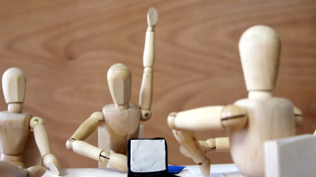 Wooden figurines having meeting in conference room video