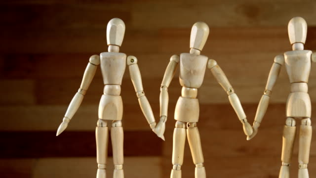Wooden figurines representing businesspeople holding hands video