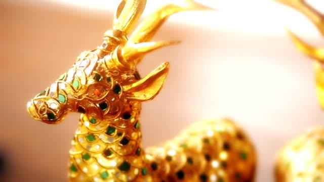 stockvideo's en b-roll-footage met houten hand gesneden hert standbeeld met goud, hout huisdecoratie beeldjes. - {{asset.href}}