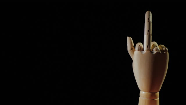 Wooden hand shows obscene gesture with middle finger on black background Wooden hand shows obscene gesture with middle finger on black background. middle finger stock videos & royalty-free footage