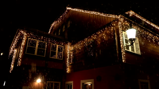 CLOSE UP: Wooden house decorated with white glowing lights on Christmas evening