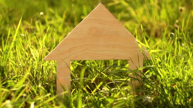 vídeos de stock e filmes b-roll de wooden house model stands in the green grass - obras em casa janelas