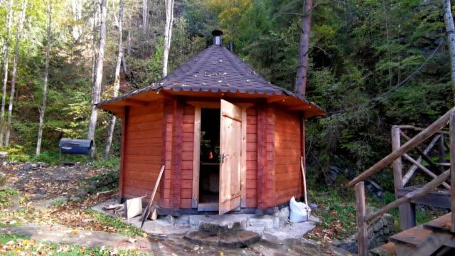 Wooden hut kitchen at small stream in a quiet dark forest