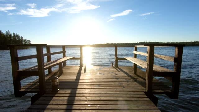 yaz aylarında orman gölünde gün batımında ahşap iskele - dalgakıran stok videoları ve detay görüntü çekimi