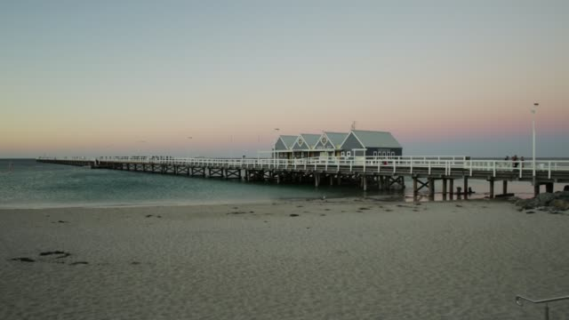 Wooden jetty at sunset Wooden jetty in Busselton Beach, Western Australia at sunset colors. Iconic landmark in Busselton, WA. jetty stock videos & royalty-free footage