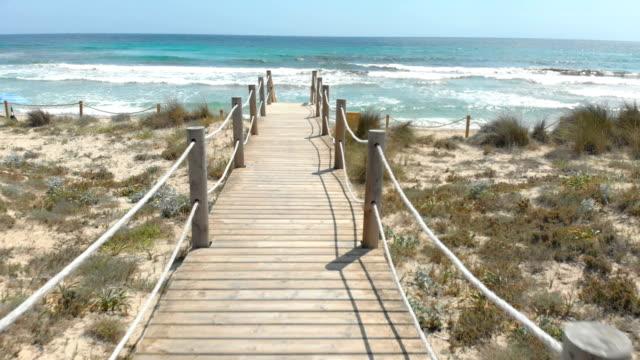 wooden jetty on a mediterranean beach in menorca, spain in summer - испания стоковые видео и кадры b-roll