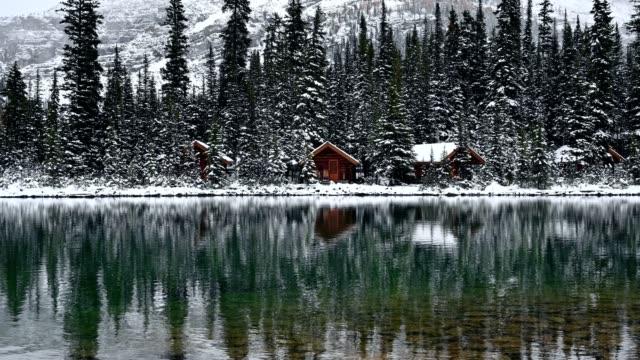 holzhütte im pinienwald mit schneebedeckter reflexion am o'hara-see im yoho nationalpark - blockhütte stock-videos und b-roll-filmmaterial