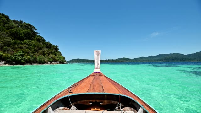 wooden long-tail boat sailing on emerald tropical sea at lipe island - phuket video stock e b–roll